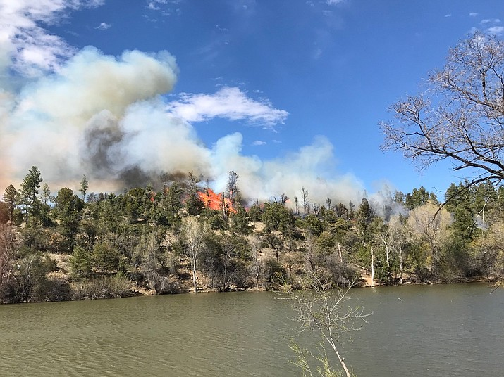 Smoke and flames rise above the treetops on the south shore of Lynx Lake Friday afternoon, April 19. Firefighters were able to contain the fire by early Friday evening.