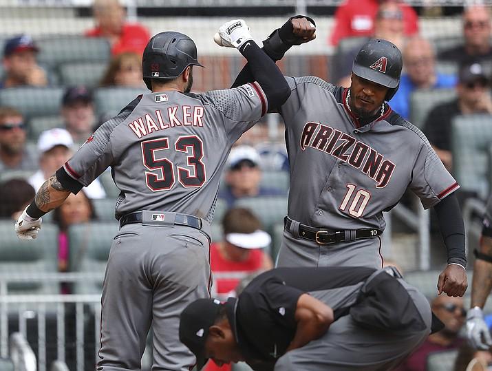 Arizona Diamondbacks' Christian Walker celebrates his 2-RBI home run with David Peralta during the seventh inning in a baseball game on Thursday, April 18, 2019, in Atlanta. (Curtis Compton/Atlanta Journal-Constitution via AP)