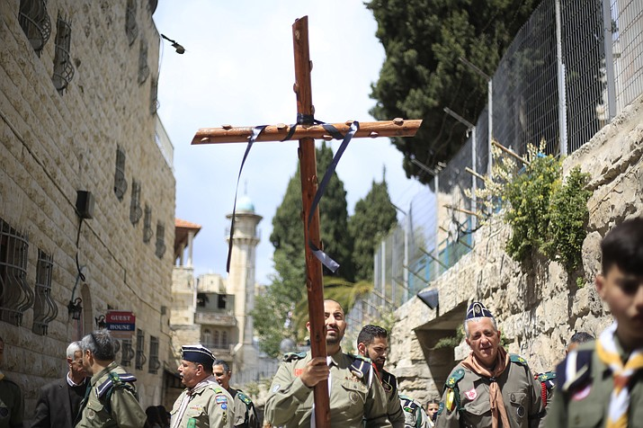 Christians from the Boy Scouts movement, one carrying a cross, walk along the Via Dolorosa toward the Church of the Holy Sepulchre, traditionally believed by many to be the site of the crucifixion of Jesus Christ, during the Good Friday procession in Jerusalem's old city, Friday, April 19, 2019. (Ariel Schalit/AP)