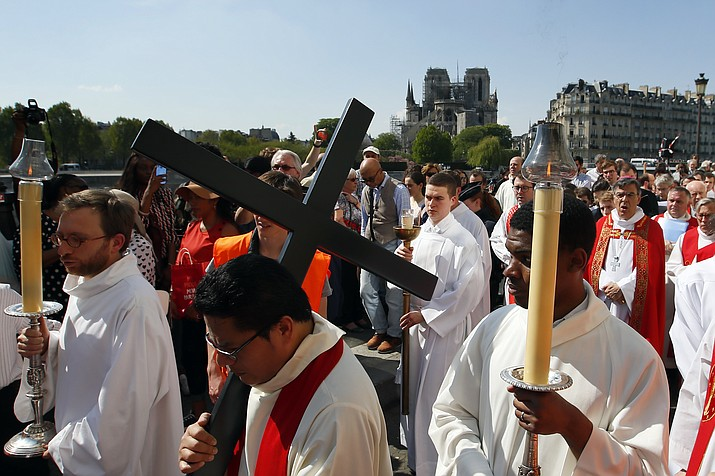 With Notre Dame cathedral in background, religious officials carry the cross during the Good Friday procession, Friday, April 19, 2019 in Paris. Top French art conservation officials say the works inside Notre Dame suffered no major damage in the fire that devastated the cathedral, and the pieces have been removed from the building for their protection.(Francois Mori/AP)