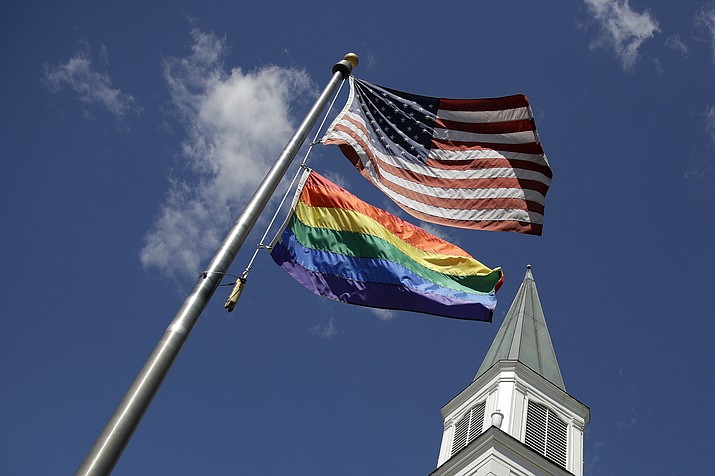 A gay pride rainbow flag flies along with the U.S. flag in front of the Asbury United Methodist Church in Prairie Village, Kan., on Friday, April 19, 2019. There's at least one area of agreement among conservative, centrist and liberal leaders in the United Methodist Church: America's largest mainline Protestant denomination is on a path toward likely breakup over differences on same-sex marriage and ordination of LGBT pastors. (Charlie Riedel/AP)