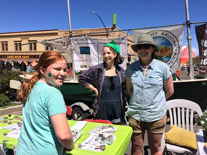 Hannah Hurley, 10, left, stops by the Earth Day table to speak with Prescott College students Camille Osburn and Taylor White in downtown Prescott Saturday, April 20. (Sue Tone/Courier)