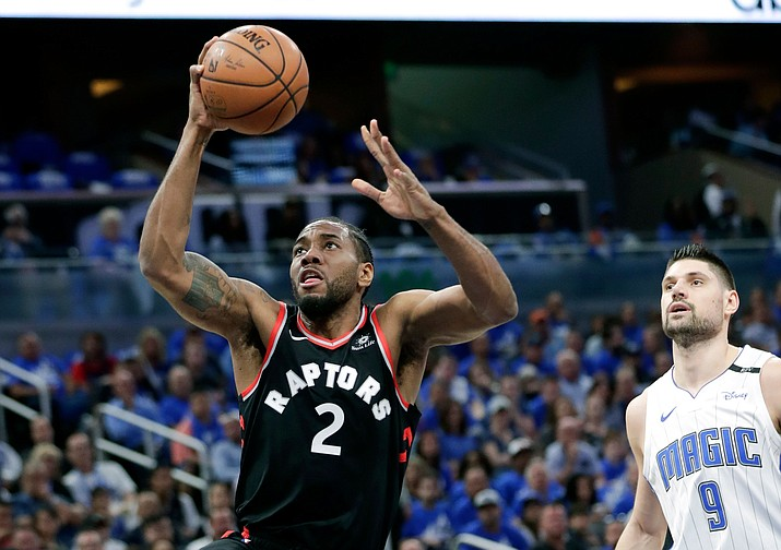 Toronto Raptors' Kawhi Leonard (2) gets a shot off as he gets past Orlando Magic's Nikola Vucevic (9) during the first half in Game 4 of a first-round NBA basketball playoff series, Sunday, April 21, 2019, in Orlando, Fla. (John Raoux/AP)