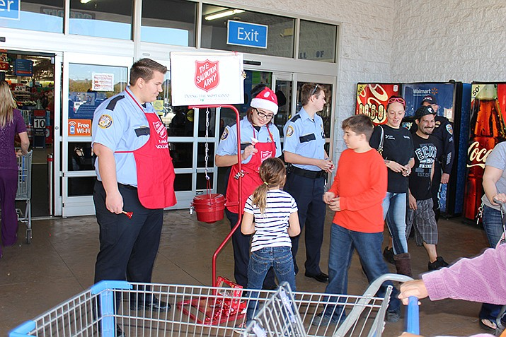 From left, Dean Curtis, Lilith Bennett and Trevin Gravell of Kingman Police Department Explorers ring the bell for the Salvation Army's Red Kettle drive in front of Walmart in this file photo. The Explorers are holding a car wash fundraiser 8 a.m. - noon Saturday, April 27 at the City of Kingman Police Department, 2730 Andy Devine Ave. (Daily Miner file photo)