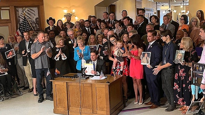 Surrounded by survivors of those killed by texting motorists, Gov. Doug Ducey signs a ban on texting while driving into law Monday, April 22, 2019, in Phoenix. (Coutesy)