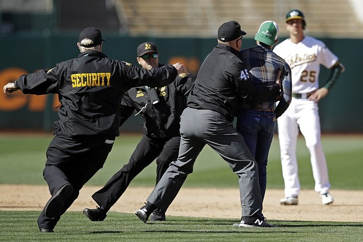 Second base umpire Jeff Nelson (45) grabs a fan that ran onto the field as security guards assist and Oakland Athletics' Stephen Piscotty, right, watches in the ninth inning of a baseball game against the Toronto Blue Jays, Saturday, April 20, 2019, in Oakland, Calif. (AP Photo/Ben Margot)