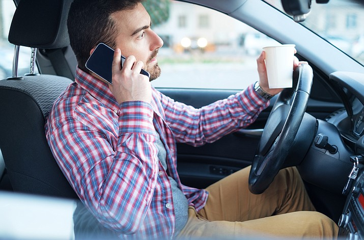 Arizona ended a decade of resistance to restrictions on using a cellphone while driving when Gov. Doug Ducey signed a law Monday outlawing holding a phone behind the wheel. (Adobe stock)
