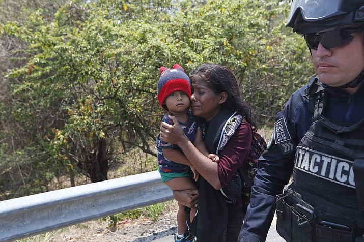 A Central American migrant woman and her son walk with a Mexican Federal Police agent as they are taken into custody on the highway to Pijijiapan, Mexico, Monday, April 22, 2019. Mexican police and immigration agents detained hundreds of Central American migrants Monday in the largest single raid on a migrant caravan since the groups started moving through Mexico last year. (Moises Castillo/AP)