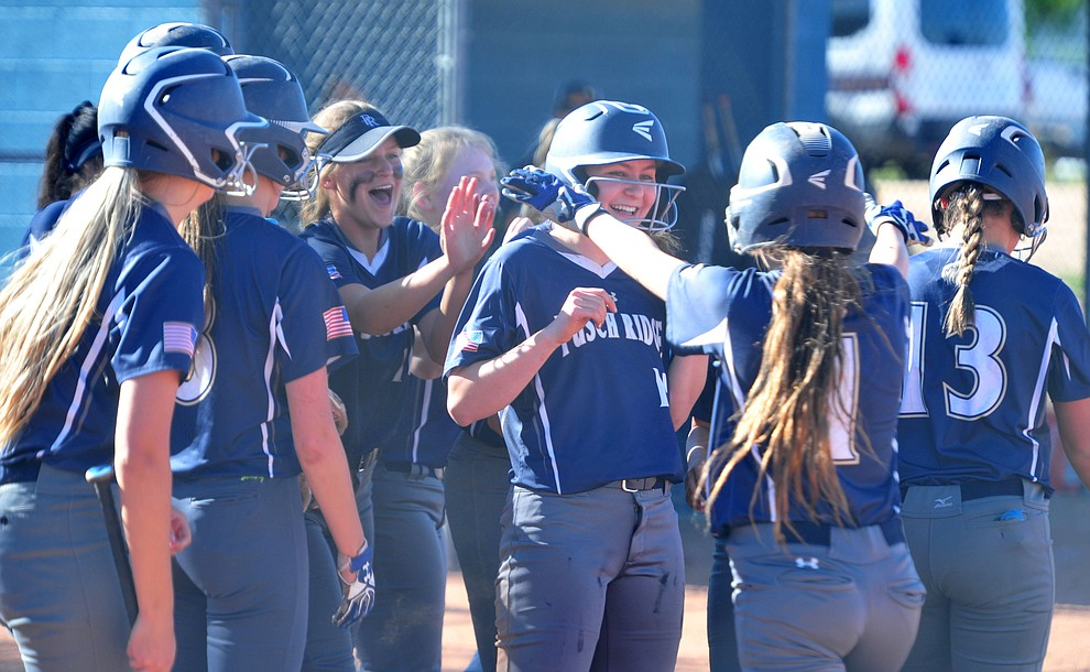 Pusch Ridge celebrates after a grand slam homerun in a 15-run second inning as they play the Chino Valley Cougars in the play-in round of the Arizona Interscholastic Association State Softball D3 Tournament Wednesday, April 24 in Chino Valley.  (Les Stukenberg/Courier)