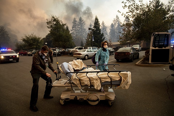 This Nov. 8, 2018, file photo shows Medical personnel evacuate patients as the Feather River Hospital burns while the Camp Fire rages through Paradise, Calif. Tens of thousands of people fled the fast-moving wildfire. (Noah Berger/AP, File)