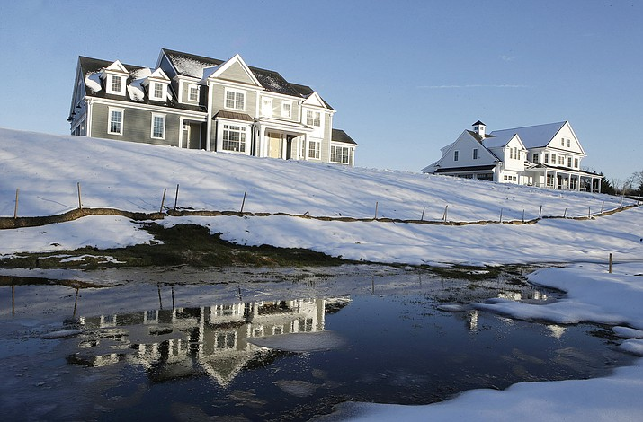 A recently constructed home is reflected in water, in Natick, Mass. Before squeezing every last nickel into a down payment on a home mortgage, set some cash aside to handle unexpected expenses after the closing. (Steven Senne/AP, file)
