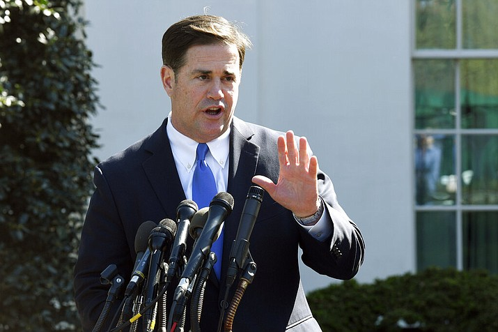In this April 3, 2019 file photo, Arizona Gov. Doug Ducey talks to reporters outside the West Wing of the White House in Washington following a meeting with President Donald Trump. Ducey is rejecting demands to take down a social media post sending Easter greetings and citing a Bible verse. The Republican who is a practicing Catholic on Thursday, April 25, 2019. posted on Twitter and Facebook his response to a Secular Communities for Arizona request to remove the Easter post from his official Facebook page. (AP Photo/Susan Walsh, File)