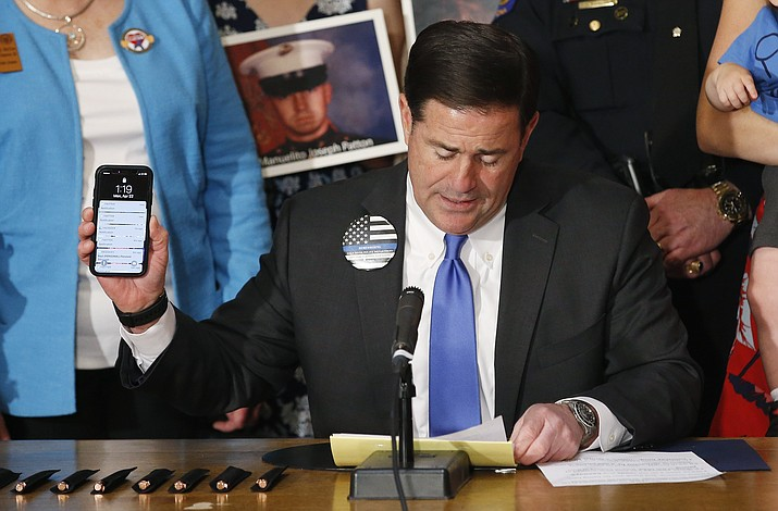 Arizona Gov. Doug Ducey speaks prior to signing into law a bill banning texting while driving Monday, April 22, at a ceremony at the Arizona Capitol in Phoenix. On Friday, April 26, Ducey vetoed a distracted driving bill, a companion bill to the cell phone bill, saying he did not want Arizonans to confuse the two. (Ross D. Franklin/AP, file)