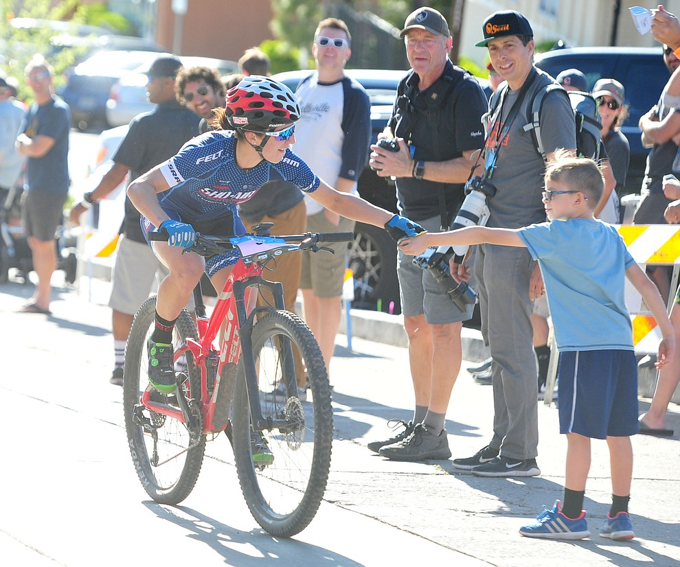 Erica Clevenger gets a hand up from a young fan during the Whiskey Off Road Fat Tire Crit through the streets of downtown Prescott Friday, April 26.  (Les Stukenberg/Courier)