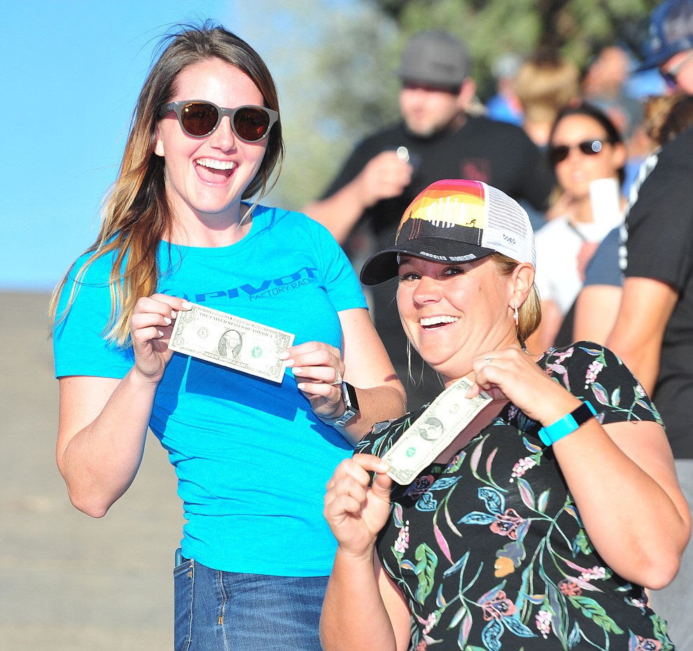 Mary Lideen and Evie Racette have their money ready for hand ups during the Whiskey Off Road Fat Tire Crit through the streets of downtown Prescott Friday, April 26.  (Les Stukenberg/Courier)