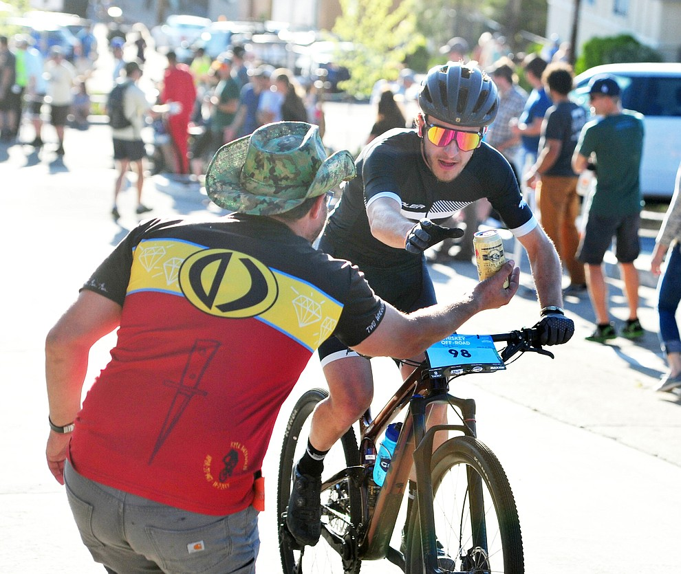 Levi Kurlander gets a beer handup during the Whiskey Off Road Fat Tire Crit through the streets of downtown Prescott Friday, April 26.  (Les Stukenberg/Courier)