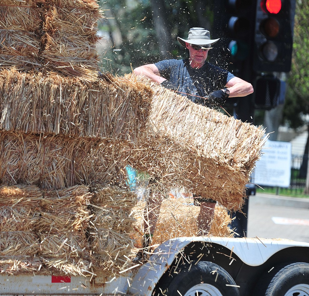 Ron Hart unloads hay bales for the Fat Tire Crit during the opening day of the Whiskey Off Road in downtown Prescott Friday, April 26.  (Les Stukenberg/Courier)