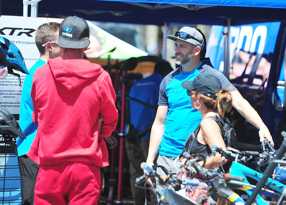 Shimano's Joe Lawwill talks to customers during the opening day of the Whiskey Off Road in downtown Prescott Friday, April 26.  (Les Stukenberg/Courier)