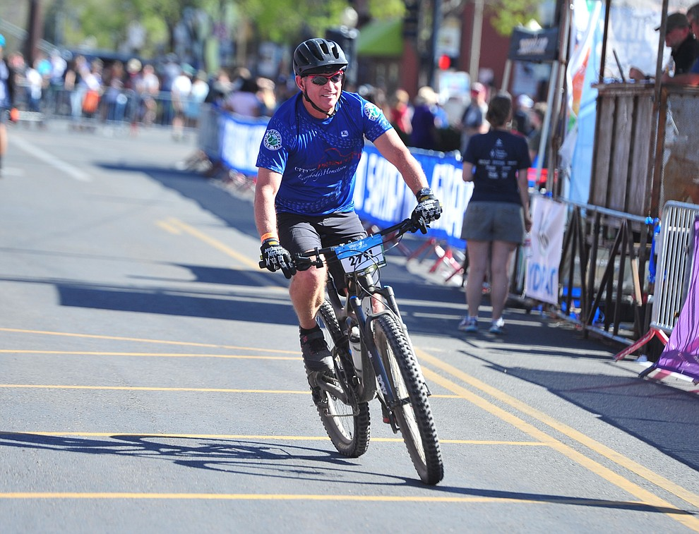 Prescott Mayor Greg Mengarelli crosses the finish line in the 15-mile race during the opening day of the Whiskey Off Road in downtown Prescott Friday, April 26.  (Les Stukenberg/Courier)