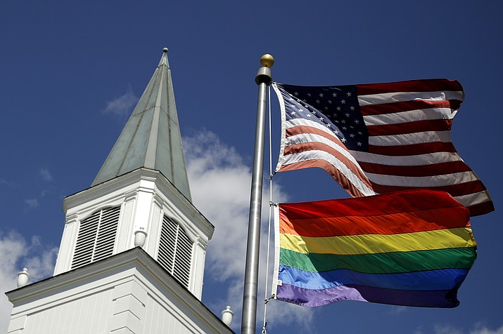 A gay pride rainbow flag flies along with the U.S. flag in front of the Asbury United Methodist Church in Prairie Village, Kan. On Friday, April 26, 2019, the United Methodist Church's judicial council upheld the legality of major portions of a new plan that strengthens the denomination's bans on same-sex marriage and ordination of LGBT pastors. (Charlie Riedel/AP)