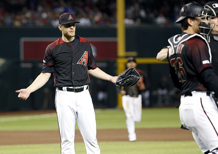Arizona pitcher Matt Koch, left, gestures toward Chicago Cubs' David Bote (not shown) as Diamondbacks catcher John Ryan Murphy (36) and home plate umpire Bill Welke, right, attempt to keep them separated after Bote was hit by a pitch during the seventh inning Saturday, April 27, 2019, in Phoenix. (Ralph Freso/AP)