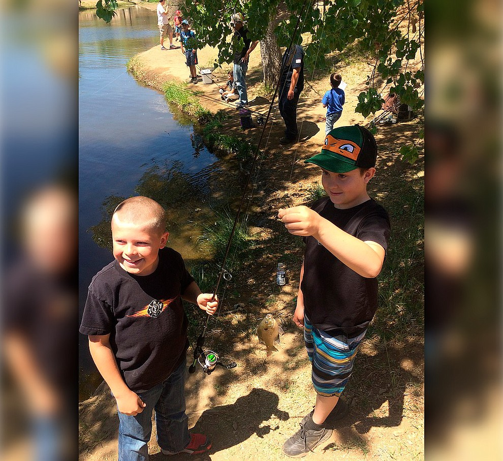 Rocco Smith and Lachlen Olson hold up a fish they caught during Badges & Bobbers at Fain Park Saturday, April 27. (Jason Wheeler/Courier)