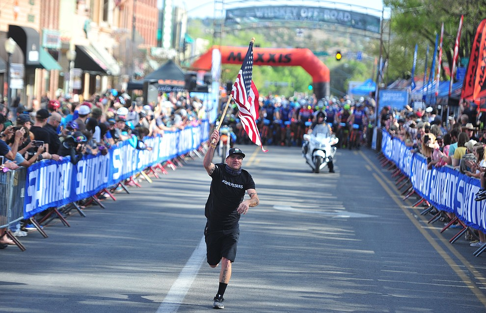 Kaolin Cummens runs the American flag up Whiskey Row before  the Whiskey Off Road Pro 50-mile cross country mountain bike race in Prescott Sunday, April 28.  (Les Stukenberg/Courier)