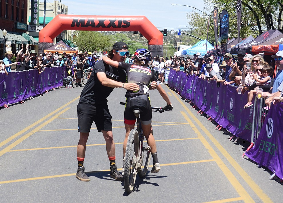 Kate Courtney gets a hug from mechanic Brad Copeland following her win at the Whiskey Off Road Pro 50-mile cross country mountain bike race in Prescott Sunday, April 28.  (Les Stukenberg/Courier)