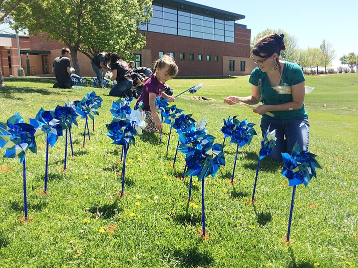 Raven Mares plants pinwheels with her mother, Diane, on Saturday, April 27, 2019, at the Prescott Valley Pinwheel Party on the Prescott Valley Civic Center Lawn. (Jason Wheeler/Courier)