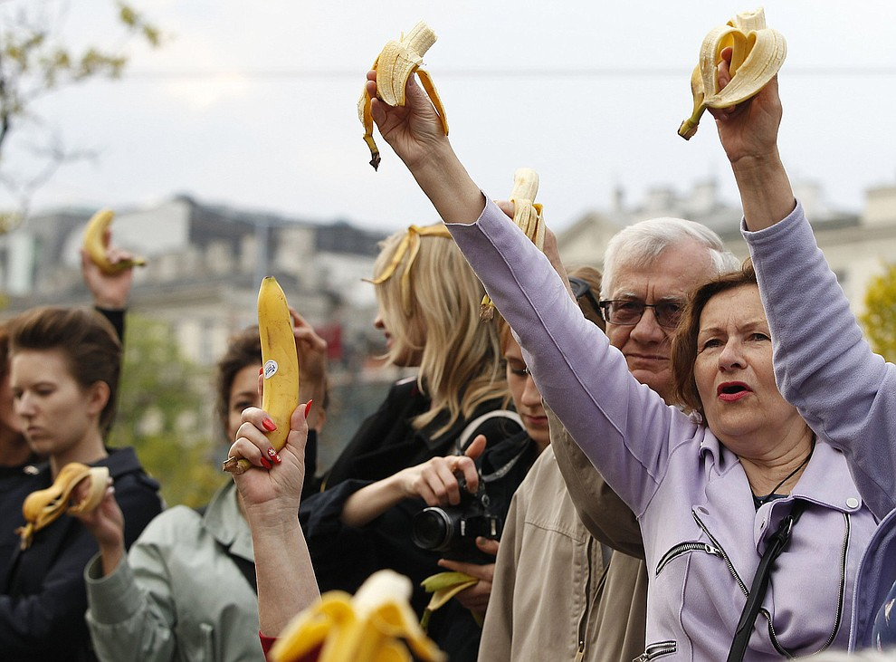 People with bananas demonstrate outside Warsaw's National Museum, Poland, Monday, April 29, 2019, to protest against what they call censorship, after authorities removed an artwork at the museum featuring the fruit, saying it was improper. (AP Photo/Czarek Sokolowski)