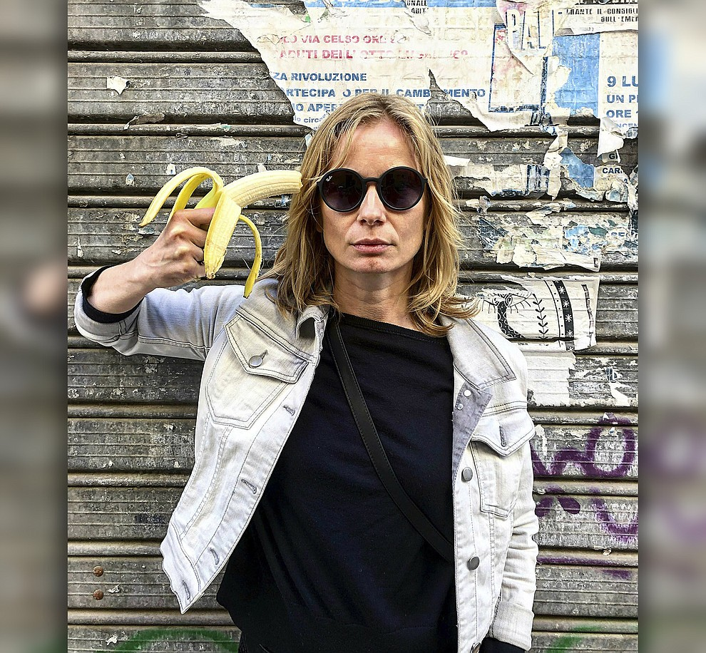 In this photo made 27 April 2019, Polish actress Magdalena Cielecka aims a banana like a gun at her head to protest the removal of an art work from the National Museum in Warsaw that features a woman eating a banana with visible pleasure, which the conservative authorities say is obscene. wld (AP Photo/Dario Salina)