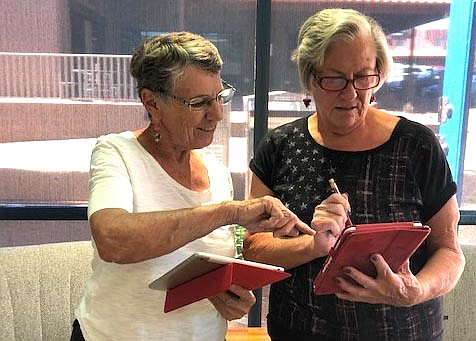 Library volunteers Holly Mason and Diane Schwilling, from left, discuss the new YLN app downloaded to their tablets.