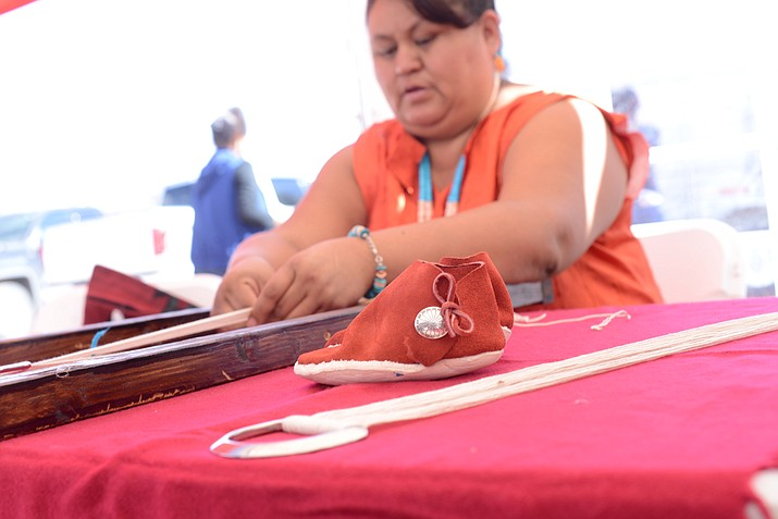 Diné Culture, Language, and Leadership graduate Kay Mariano works on a sash belt while displaying a moccasin she made. (Photo courtesy of NTU)