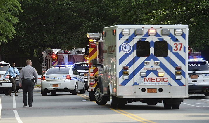 Emergency vehicles cluster on Mary Alexander Road on the campus of University of North Carolina at Charlotte after a shooting Tuesday, in Charlotte, N.C.  (John Simmons/The Charlotte Observer via AP)