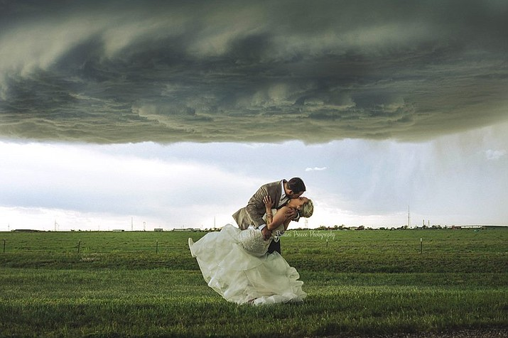 Manuel and Morgan Monteiro kiss under a large supercell. (Photo by Brittani Preece Photography)