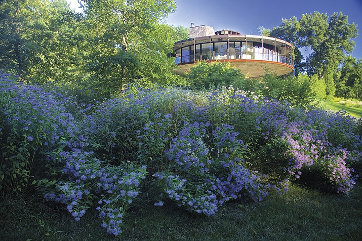 """This photo provided by Rizzoli Press shows Round House by Richard Foster and a wild flower garden in Wilton, Conn. The photograph is featured in the book """"Garden Wild: Wildflower Meadows, Prairie-Style Plantings, Rockeries, Ferneries, and Other Sustainable Designs Inspired by Nature"""" by Andre Baranowski. (Andre Baranowski/Rizzoli Press via AP)"""