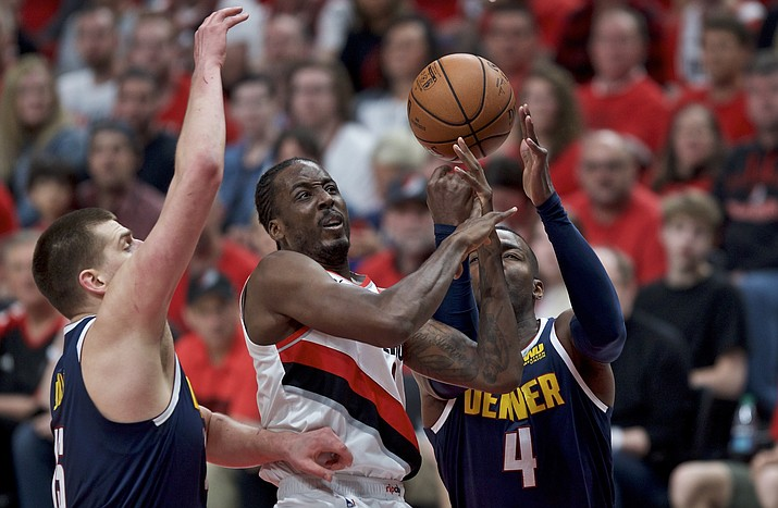 Portland Trail Blazers forward Al-Farouq Aminu, center, shoots between Denver Nuggets forward Paul Millsap, right, and center Nikola Jokic, left, during the first half of Game 4 of an NBA second-round playoff series Sunday, May 5, 2019, in Portland, Ore. (Craig Mitchelldyer/AP)