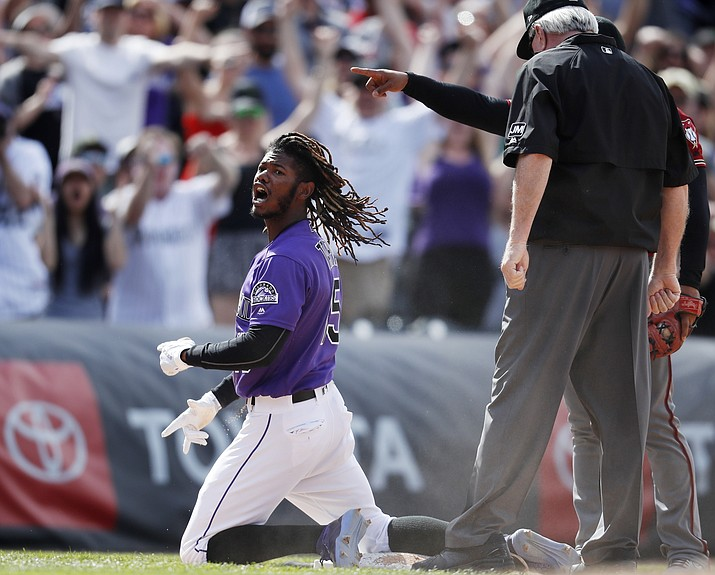 Colorado Rockies' Raimel Tapia reacts after hitting a triple to drive in three runs off Arizona Diamondbacks relief pitcher Archie Bradley in the eighth inning of a baseball game Sunday, May 5, 2019, in Denver. (David Zalubowski/AP)
