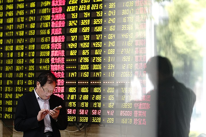 A man looks at his smartphone near a display showing stock prices at a brokerage house in Shanghai Monday, May 6, 2019. China's benchmark Shanghai Composite index dives on U.S. President Donald Trump threat of more China tariffs. At right is a reflection off a display board. (AP Photo)
