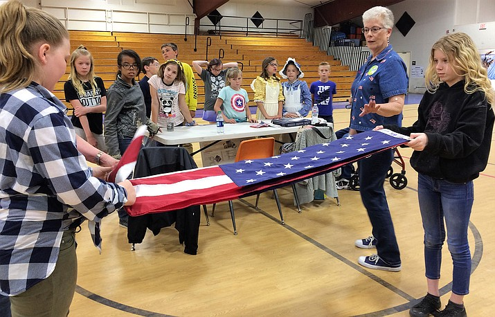 Humboldt Elementary School fifth-graders Ella Delozier, left, and Lilly Porter learn proper flag-folding etiquette from Mary LaValley and Cindy Mackie (outside photo at left) during the annual Pioneer Day event at the school. (Sue Tone/Tribune)