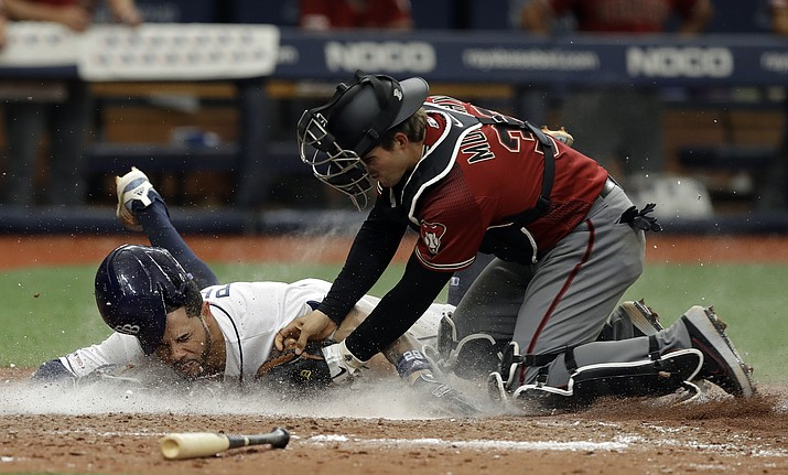 Tampa Bay Rays' Tommy Pham, left, gets tagged out by Arizona Diamondbacks catcher John Ryan Murphy at home plate while trying to score on an RBI-single by Kevin Kiermaier during the ninth inning of a baseball game, Wednesday, May 8, 2019, in St. Petersburg, Fla. (Chris O'Meara/AP)