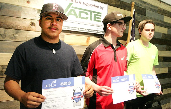 Valley Academy construction students Edgar Arreola, Jared Byler and Dylan White, from left, hold their employment certificates Wednesday at SkillsUSA National Signing Day. VVN/Bill Helm
