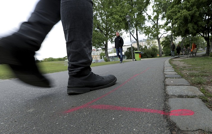 A man walks past a so called 'Drug Dealer Area' next to a traffic training course for kids at the public Goerlitzer Park in Berlin, Germany, Thursday, May 9, 2019. (AP Photo/Michael Sohn)