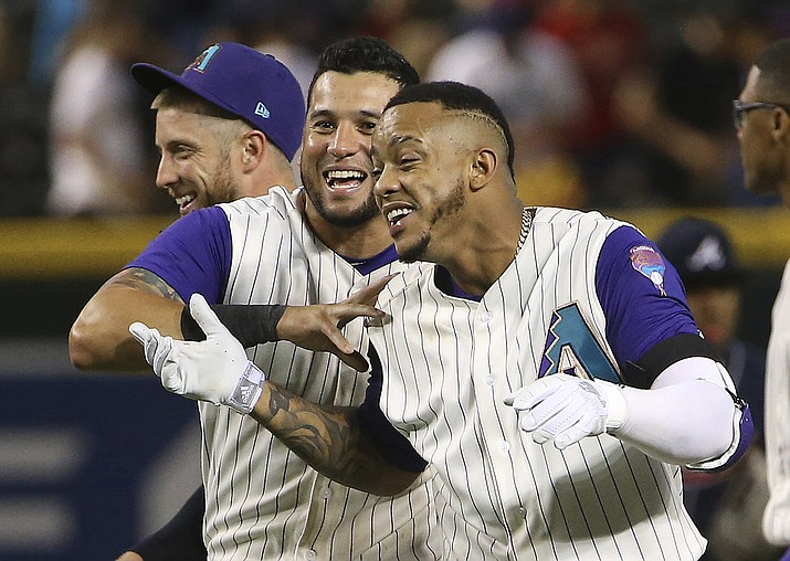 Arizona Diamondbacks' Ketel Marte, right, celebrates his walk-off single against the Atlanta Braves in the 10th inning with David Peralta, middle, and Merrill Kelly, left, in a baseball game Thursday, May 9, 2019, in Phoenix. The Diamondbacks won 3-2. (Ross D. Franklin/AP)
