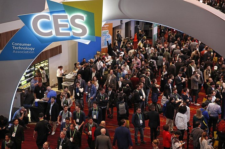 "In this Jan. 9, 2018, file photo, people attend CES International in Las Vegas. The Consumer Technology Association on Wednesday, May 8, reinstated an award to the makers of a robotic ""personal massager"" for women that it had taken away four months ago for not keeping with its image. (AP Photo/John Locher, File)"