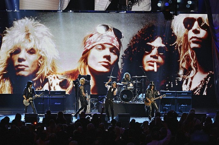In this 2012, file photo, Guns N' Roses performs with singer Myles Kennedy after their induction into the Rock and Roll Hall of Fame in Cleveland. The rock band is accusing a Colorado brewery of stealing their brand and piggybacking off their fame to sell beer and merchandise. The band filed a trademark infringement lawsuit Thursday, May 9, 2019, against Colorado-based Oskar Blues Brewery, which sells Guns 'N' Rosé beer and merchandise, including bandannas the group says is uniquely associated with singer Axl Rose. (AP Photo/Tony Dejak, File)
