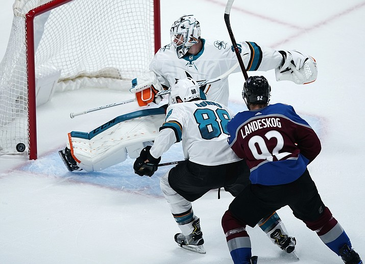 San Jose Sharks goaltender Martin Jones, back, makes a kick-save of a shot as defenseman Brent Burns, center, and Colorado Avalanche left wing Gabriel Landeskog pursue the puck in the first period of Game 6 of a second-round playoff series Monday, May 6, 2019, in Denver. (Jack Dempsey/AP)