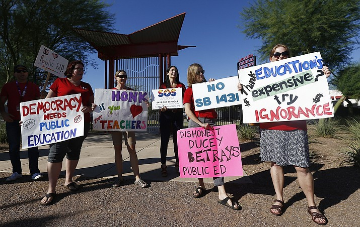 In this Aug. 24, 2017, file photo, members of Save Our Schools Arizona protest at the Arizona School for the Arts as Arizona Gov. Doug Ducey tours the school in Phoenix. (Ross D. Franklin, File/AP)