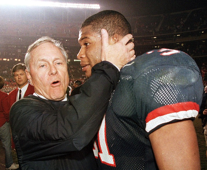 Arizona coach Dick Tomey, left, congratulates linebacker DaShon Polk after the Wildcats 23-20 win over Nebraska in the Holiday Bowl on Dec. 30, 1998, in San Diego. Tomey, the winningest football coach in University of Arizona history, died Friday night, May 10, 2019, in Tucson, Ariz. He was 80. Tomey was 183-145-7 overall in 20 years as head coach at Hawaii, Arizona and San Jose State. He was diagnosed with lung cancer in December. (Denis Poroy/AP, File)