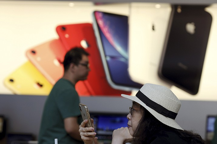 A customer looks at her iPhone in a store of U.S. tech company Apple in Beijing on Friday, May 10, 2019. U.S. President Donald Trump's latest tariff hike on Chinese goods took effect Friday and Beijing said it would retaliate, escalating a battle over China's technology ambitions and other trade tensions. (Ng Han Guan/AP)